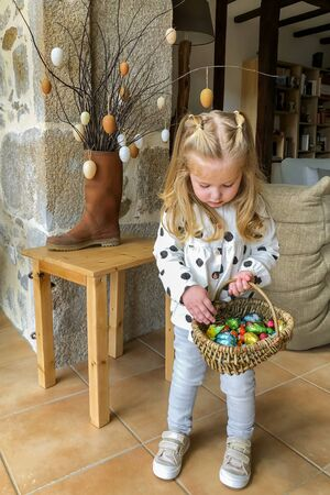 Girl holding basket with eggs for easter