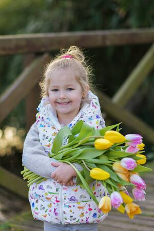 Portrait of a blonde girl with a bouquet of tulips in her hands 版權商用圖片