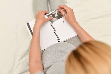 Pregnant woman holding ultrasound image and makes the notes in a notebook. Expectation of a child