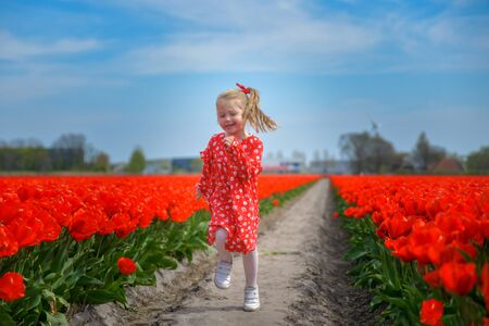 Girl running in a red tulip field