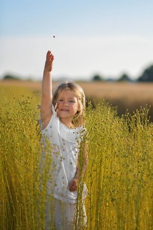 A girl in a white dress in a field of flax