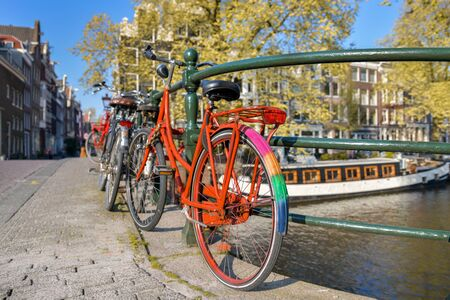Orange bike with LGBT flag parked on a bridge in Amsterdam, Netherlands Stockfoto
