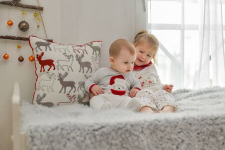 Brother and sister in Christmas pajamas are sitting on the bed. Stockfoto