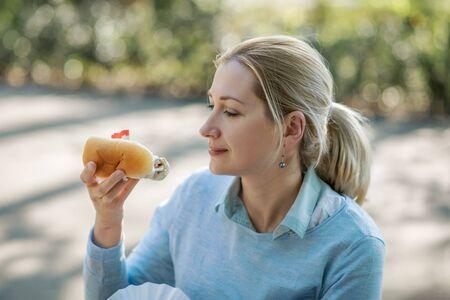Dutch blonde woman eating fresh harring standing outdoors in Amsterdam Standard-Bild