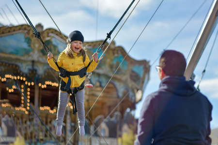 A smilling girl jumping on a trampoline with insurance.