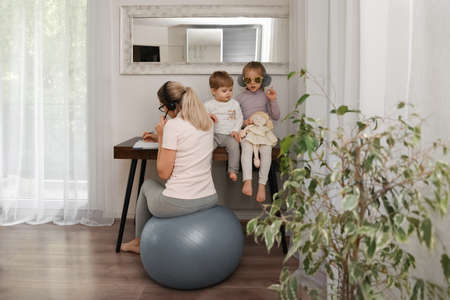 Mother sits on a fitness ball in headphones and works at home with her children during quarantine Covid-19