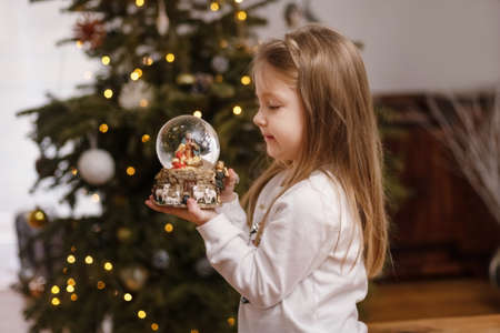 Girl looking at a glass ball with a scene of the nativity of Jesus Christ in a glass ball