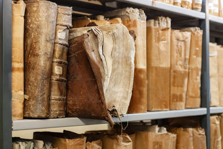 Old worn 17th century books on a shelf in the library's archives Foto de archivo