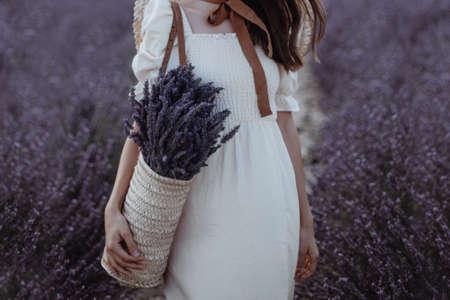 Woman holding wicker basket with a lavender in the field Foto de archivo