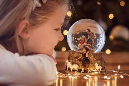 Girl looking at a glass ball with a scene of the nativity of Jesus Christ in a glass ball on a Christmas tree