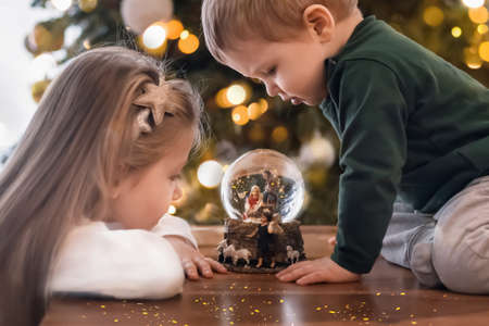 Sister and brother looking at a glass ball with a scene of the nativity of Jesus Christ in a glass ball on a Christmas tree Foto de archivo