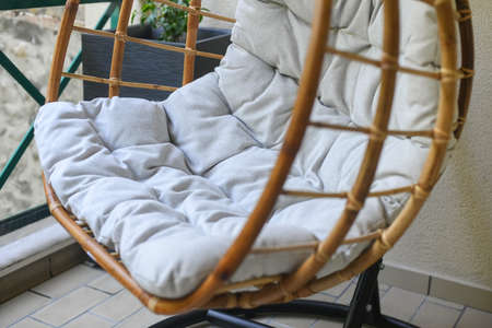 Bamboo chair with gray cushion hanging on the balcony Foto de archivo