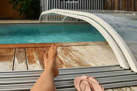 Woman legs by the outdoor pool