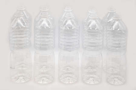 Row of plastic mineral water bottles isolated on a white background.