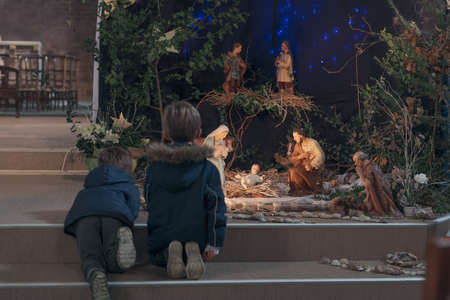 Children look at christmas creche with Joseph Mary and small Jesus Foto de archivo