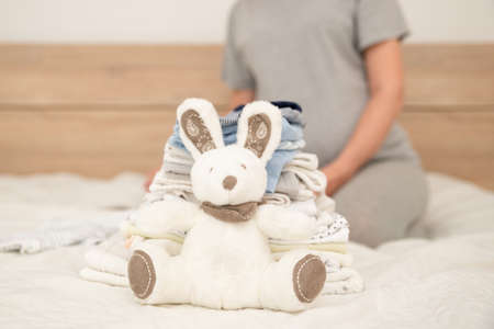 Pile of baby clothes, rabbit and pregnant woman