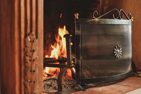 Fire in a french old fireplace with a fire shield Foto de archivo