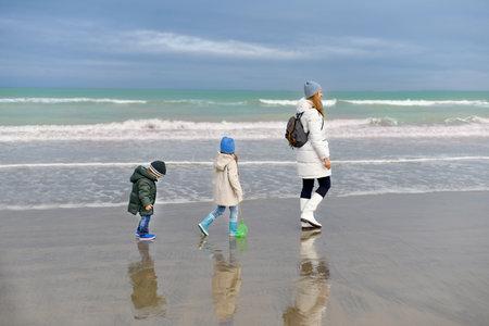 Mother and her children walking along at Atlantique ocean Foto de archivo