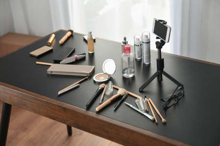 Cosmetics and makeup brushes on the desk of blogger