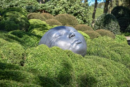 ETRETAT, FRANCE - SEPTEMBER 02, 2018: Giant rubber heads sleeping on green pillows. Boxwood garden in the famous garden of Etretat, Normandy Editorial