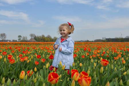 Happy girl running in an orange tulip field