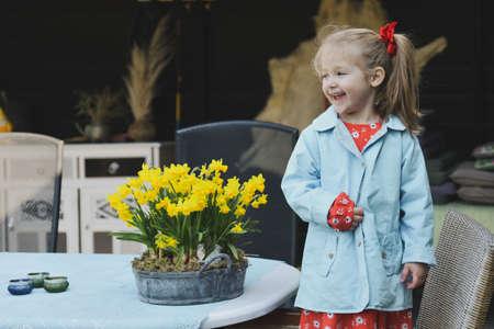A girl in a dress near a pot of daffodils