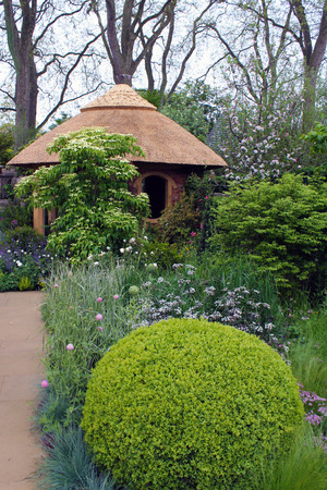 Landscape Design Garden Design - Thatched shed surrounded by planting.