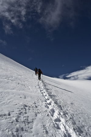 Saas Fee: alpinists climbing allalinhorn in swiss alps Stock Photo