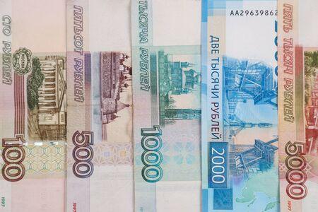 Banknoty rosyjskich pieniędzy o nominałach 100, 500, 1000, 2000, 5000 rubli, ułożone pionowo.