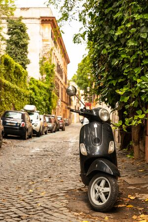 Black Vespa scooter parked on the street in Rome. Rome, Italy, May 2019.