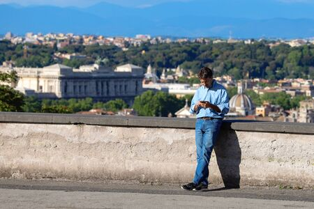 An adult man looks at his phone on the street, with a panorama of the city of Rome in the background. Rome, Italy, May 2019.