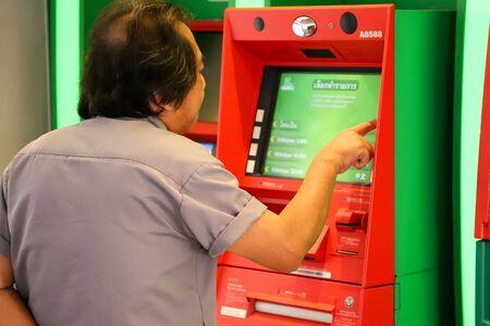 Eelderly man uses an ATM. Thailand Bangkok March 2020