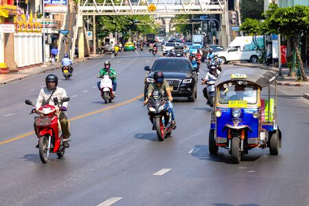 Car traffic on the road in Bangkok day tuk-tuk taxi tricycle, motorcycles, cars, Rama i road. Thailand Bangkok March 2020