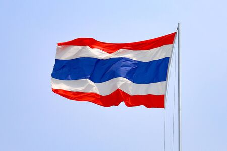 The flag of Thailand against the blue sky flutters in the wind.