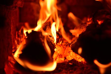 Tongues of tortuous flame rise above the burning wood, turning them into red coals.