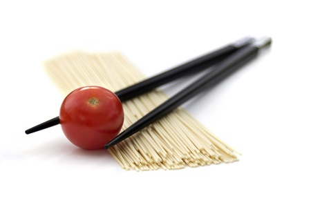 Japan noodles with chopsticks and cherry tomato isolated on white