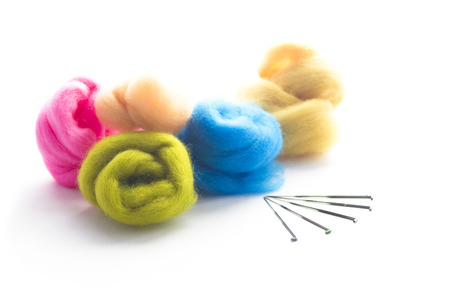 Colorful wool tops with felting needles isolated on white