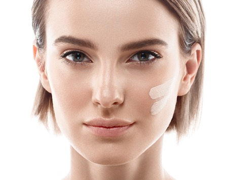 Skin tone cream lines on woman face. Beautiful woman portrait beauty skin healthy and perfect makeup. Studio shot. Isolated on white. Banque d'images