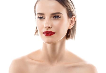 Mujer cara de la belleza del retrato. Bella modelo chica con labios de color piel perfecta fresco y limpio de color rojo púrpura. Morena Rubia pelo corto juventud y la piel del concepto de atención. Aislado en un fondo blanco