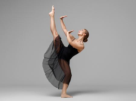 Ballet dancer woman black dress on gray background. Studio shot.