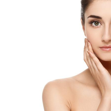 きれいな新鮮な完璧な健康的な肌を持つ若い女性モデルの美しいハーフ顔。年齢と健康概念。白で隔離美容女性の肖像画