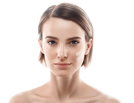 Skin tone cream lines on woman face. Beautiful woman portrait beauty skin healthy and perfect makeup. Studio shot. Isolated on white. Foto de archivo