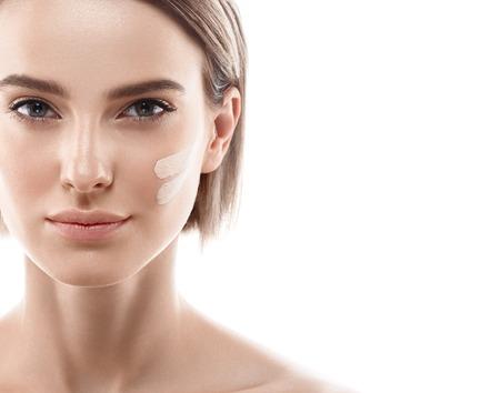 女性の顔にクリーム皮膚トーン ライン。美しい女性の肖像画の美しさは肌健康的で完璧なメイクです。スタジオ撮影します。白で隔離。