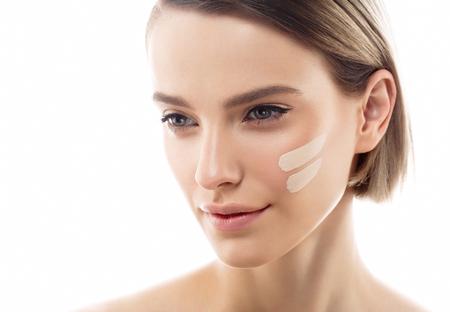 여자 얼굴에 피부 톤 크림 라인. 아름 다운 여자의 초상화 아름다움 피부를 건강하고 완벽한 메이크업. 스튜디오 촬영. 흰색입니다.