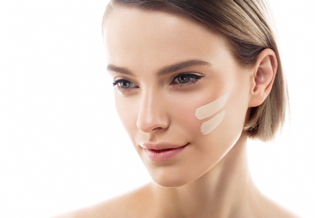 Skin tone cream lines on woman face. Beautiful woman portrait beauty skin healthy and perfect makeup. Studio shot. Isolated on white. Archivio Fotografico