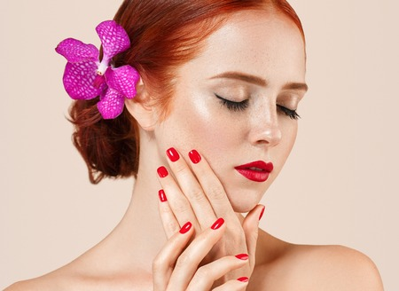 beige lips: Beautiful woman portrait with flower in hair perfect make up manicure red lips and nails on beige background isolated Stock Photo