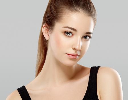 Beautiful woman face close up portrait young. Studio shot. Gray background.