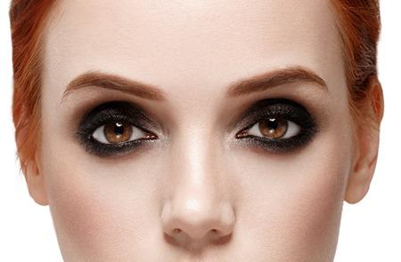 smoky black: Eyes woman. Smoky black make up on eyes. Beautiful portrait. Close up view. Isolated on white.