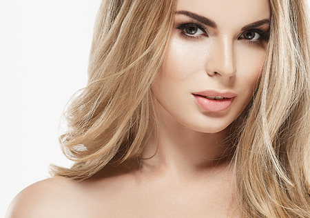salud sexual: cara de mujer hermosa joven de cerca retrato de estudio en blanco con el pelo largo y rizado rubia asombrosa Foto de archivo