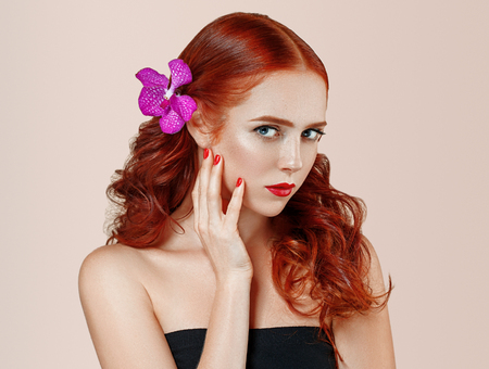 Beautiful woman portrait with flower in hair perfect make up manicure pink lips and nails on beige background isolated 写真素材